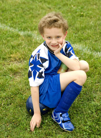 uniform curls: Young soccer player sitting on ball on sideline waiting turn