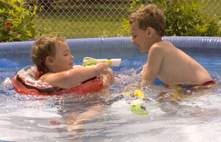 Young boy squirting water gun while playing in pool with brother