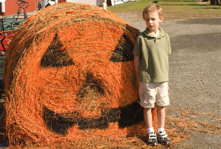 curls: Young boy standing in front of large straw pumpkin