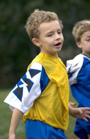 uniform curls: Young boy playing soccer on field