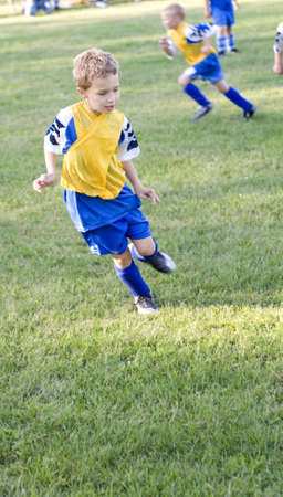 uniform curls: Young soccer player getting in position to steal ball on field