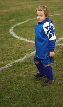 uniform curls: Young soccer player walking on field in uniform
