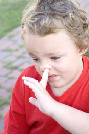 Young blond boy picking nose with index finger