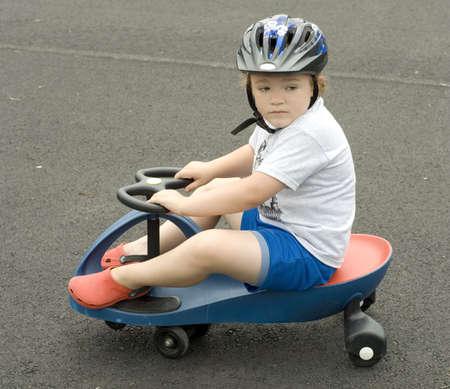 Young boy riding blue plasma car on asphalt