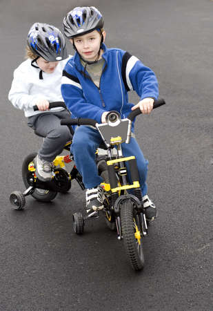 Two young boys riding bicycles wearing helmets photo