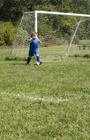 Young soccer player doing goal kick photo