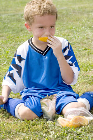 snack: Young soccer player eating orange during halftime Stock Photo