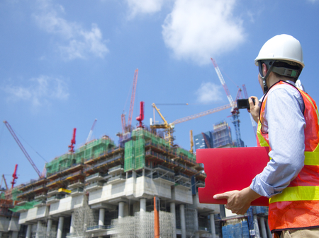 Construction worker taking photos with a red file