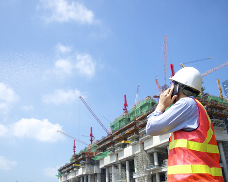 Construction worker talking on a smart phone Imagens
