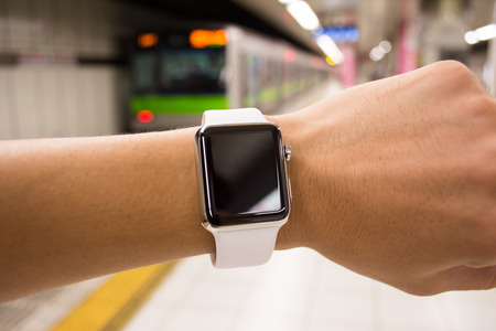 An Asian man using his smart watch at a station