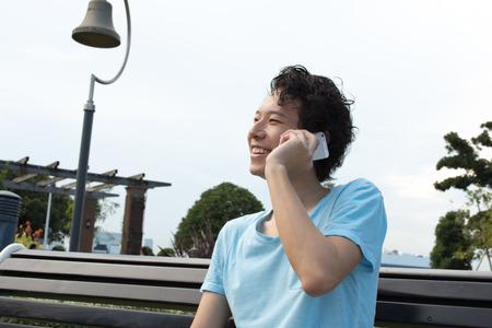 笑顔でスマート フォンで話す男