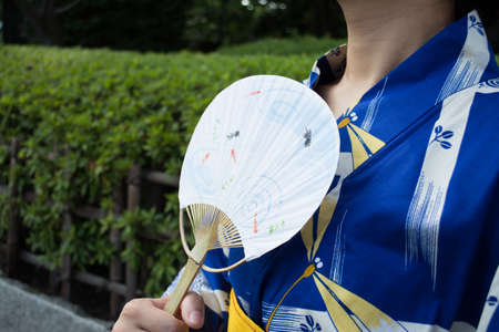 paper fan: A woman wearing Kimono is holding a paper fan Stock Photo