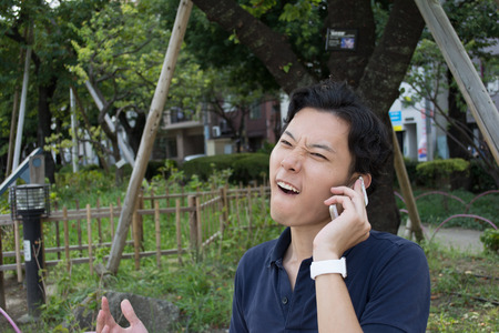 Angry Asian businessman is talking on a phone Stock Photo