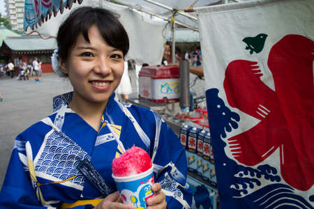 snow cone: A woman wearing Yukata is eating a snow cone