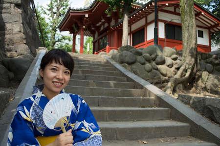 japanese fan: A woman wearing Yukata is holding a Japanese fan