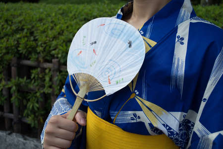 paper fan: A woman wearing Yukata is holding a paper fan
