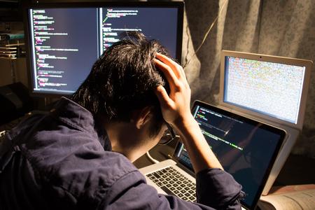 コンピューターの画面を見てアジアの過労のエンジニアを強調