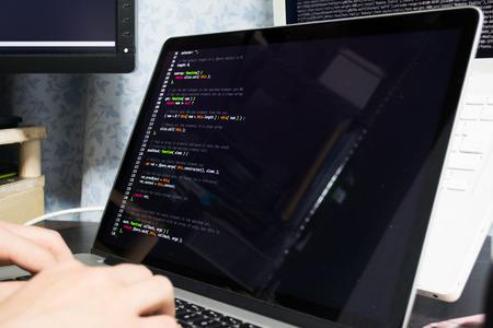 アジアのエンジニアがコンピューターのプログラムを書く 写真素材