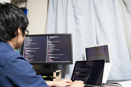 programme: Asian engineer writing a programme on a computer