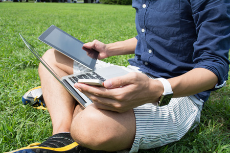 Young Asian freelance man using multiple devices at a park