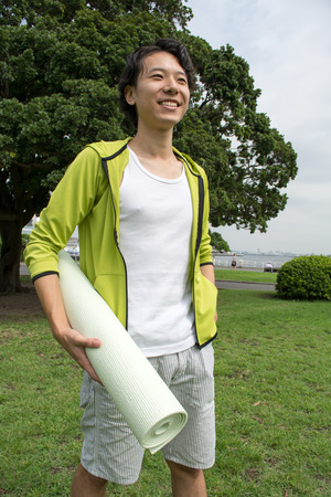 yoga pants: Young Asian man with a gym mat in the park Stock Photo