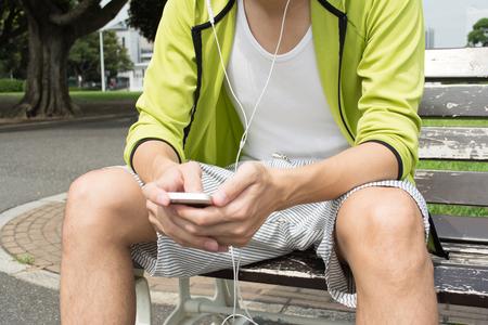 フィットネスの男性が公園で音楽を聴く
