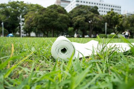 Green yoga mat on green grass, close up photo