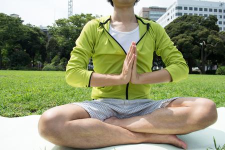 Jonge Aziatische geschiktheidsmens die yoga buiten op gras doet