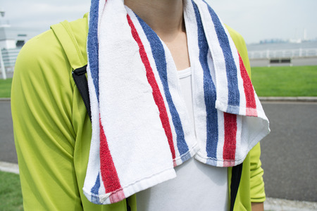 Jonge Aziatische vrouw met behulp van een handdoek na de training in een park