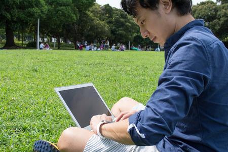 Jonge Aziatische freelance man het controleren van zijn SmartWatch bij een park Stockfoto