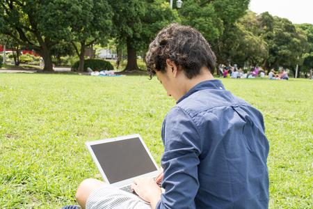 Jonge Aziatische freelance man met een pc in een park