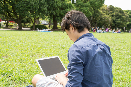 Young Asian freelance man using a pc at a park