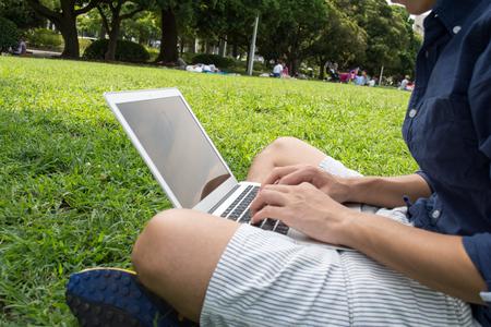 アジア系の若いフリーランスの公園で pc を使用している人