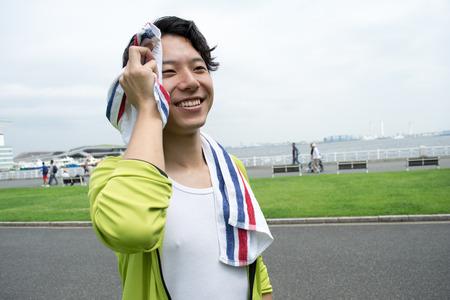 運動公園のタオルを使用して若いアジア女性