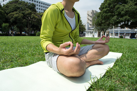 yoga outside: Young Asian fitness man doing yoga outside on grass