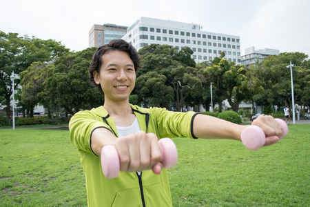 Young Asian fitness man doing workout outside on grass Stock Photo