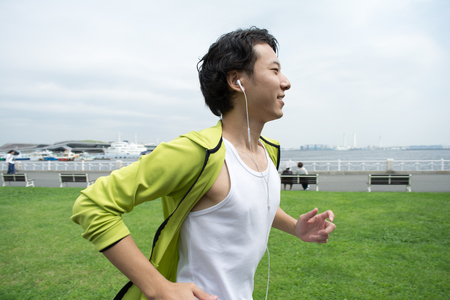 Happy young asian man running in city park
