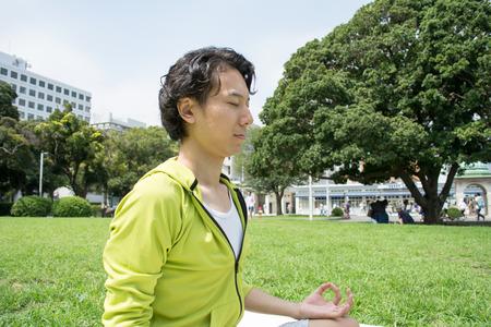芝生の上の外ヨガ若いアジア フィットネス男