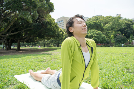 Young Asian fitness man doing yoga outside on grass