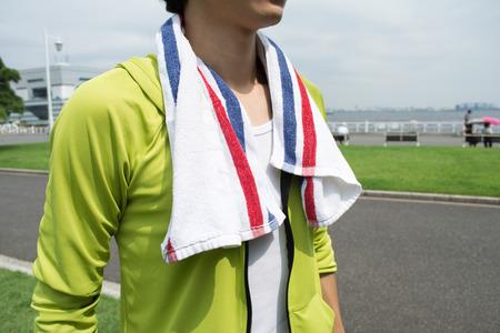 運動公園のタオルを使用して若いアジア男