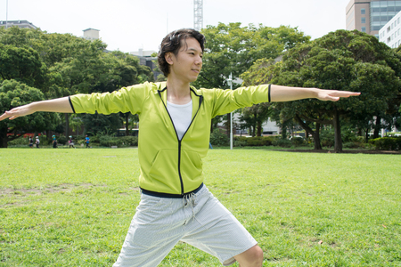 Jonge Aziatische fitness man doen yoga buiten op gras Stockfoto