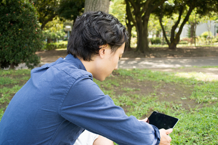 Young Asian freelance man using a tablet at a park Stock Photo