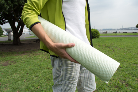 Young Asian man with a gym mat in the park Imagens