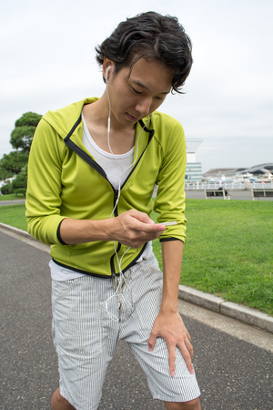 Young Asian fitness man runner using his smartphone at a park Imagens