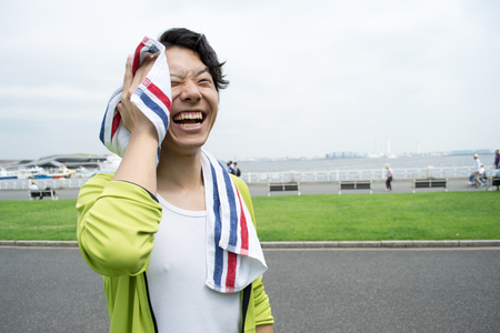 Young Asian man using a towel after exercise at a park