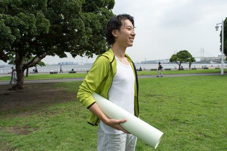 Jonge Aziatische man met een fitnessruimte mat in het park