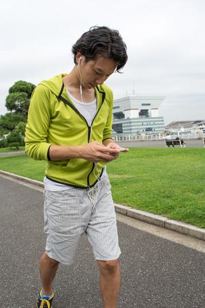 若いアジア フィットネスの男性ランナーの公園で彼のスマート フォンを使用して 写真素材