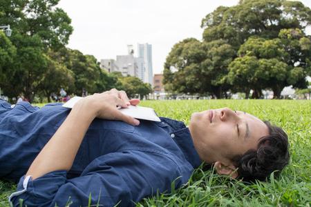 Jonge Aziatische freelance man slapen op het gras Stockfoto