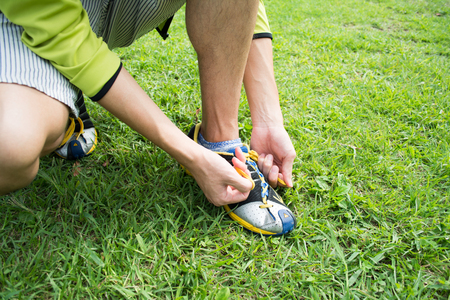 Young man tying sports shoe at a park Imagens