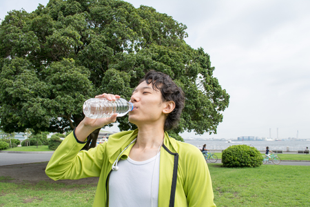 Young Asian man drinking water before running Imagens